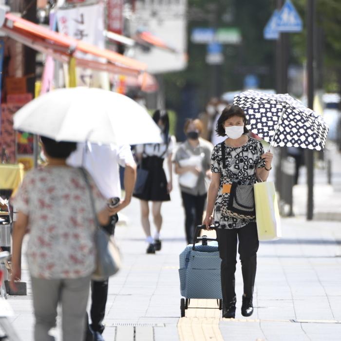 炎天下で日傘を差し、マスクを着けて歩く人たち=甲府市内