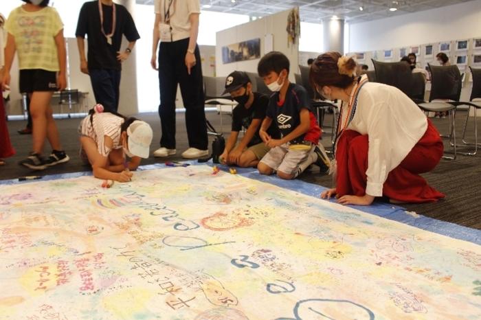 「平和アート」のコーナーでメッセージやイラストを書き込む来場者ら=甲府・県立図書館