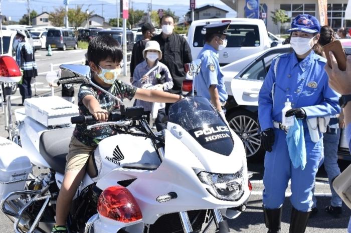 展示されている白バイにまたがる子ども=昭和・イオンタウン山梨中央