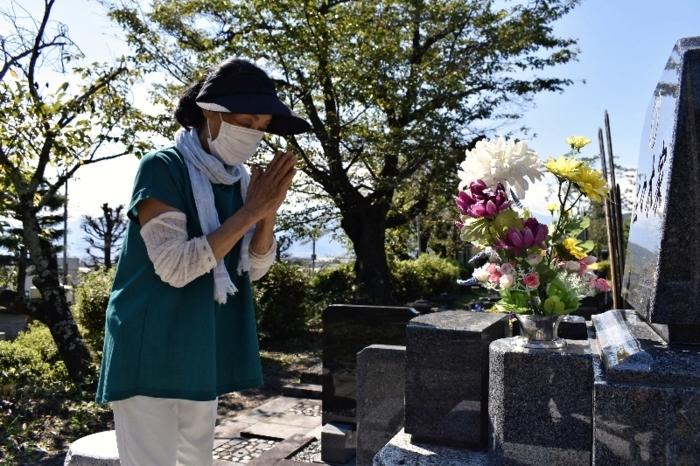 墓前に手を合わせる人=甲府・つつじが崎霊園