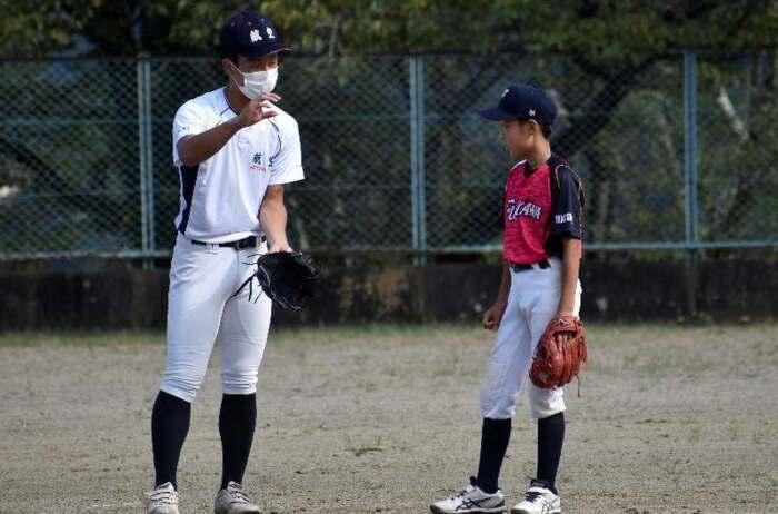 自身が小学生時代に所属していた富士川野球スポーツ少年団の選手にアドバイスする久次米陸士選手(左)=富士川・大法師公園