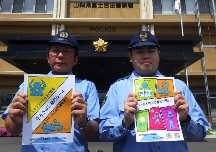 ピクトグラムを用いて製作したチラシを持つ似顔絵捜査員(左)とサイバー捜査員=富士吉田署