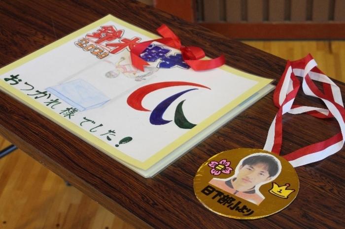 児童が手作りした金メダルと寄せ書き=山梨・日下部小