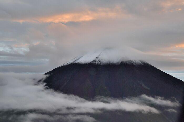 雪化粧した富士山。山頂は雲に覆われていたが、中腹についた雪を確認できた=山日YBSヘリ「ニュースカイ」(NEWSKY)から