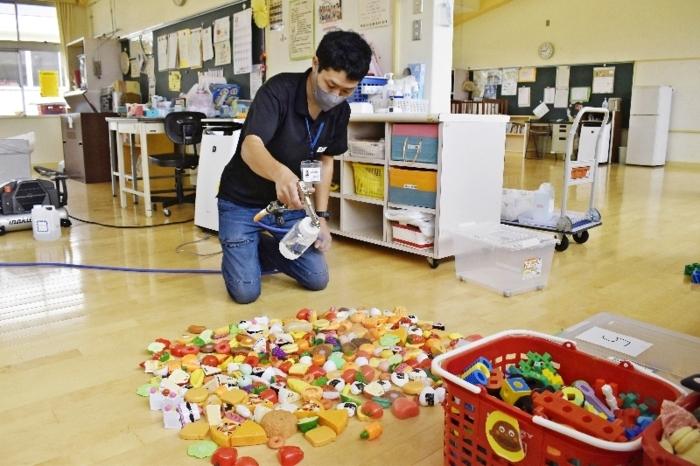 おもちゃに菌を不活性化させるコーティング剤を散布する作業員=南アルプス市立白根保育所