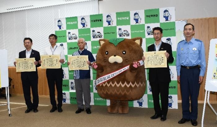 記念撮影する(左から)山田顕治さん、仲山斉さん、山田守さんら=甲斐署